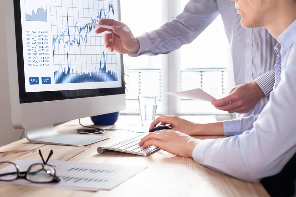 Two persons discussing and looking at graphs – Finance brokerage