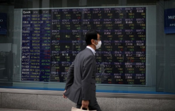 FILE PHOTO: A man wearing protective face mask, following an outbreak of the coronavirus disease (COVID-19), walks in front of a stock quotation board outside a brokerage in Tokyo, Japan, March 10, 2020. REUTERS/Stoyan Nenov